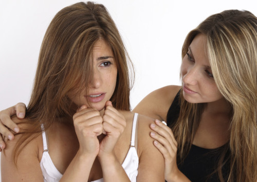 Hypnotherapy treatment for fears and phobias - young woman comforts frightened female friend