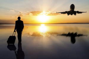 fear of flying therapy - pilot standing with hand lugguage looking at sunset with plane taking off to the right