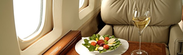 Fear of flying Hypnotherapy - Aeroplane first class seat with delicious fresh salad and white wine on table