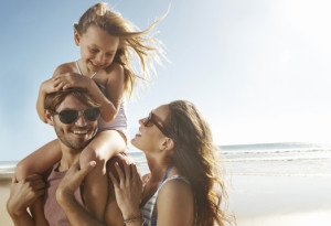 Happy couple on beach with child after successful fear of flying hypnotherapy treatment