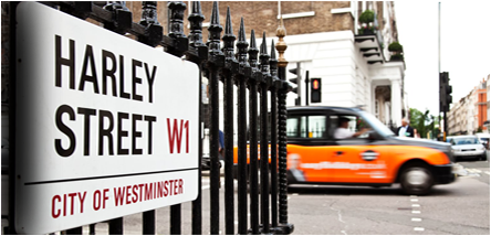 Harley Street sign with blurred Taxi in background