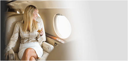 fear of flying hypnosis treatment - happy woman on private jet with champagne looking out of window