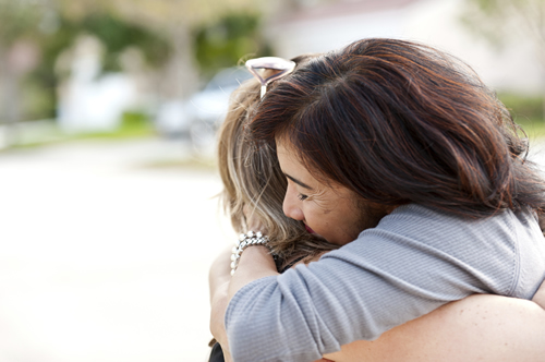 two women hug after successful fear of flying hypnotherapy treatment